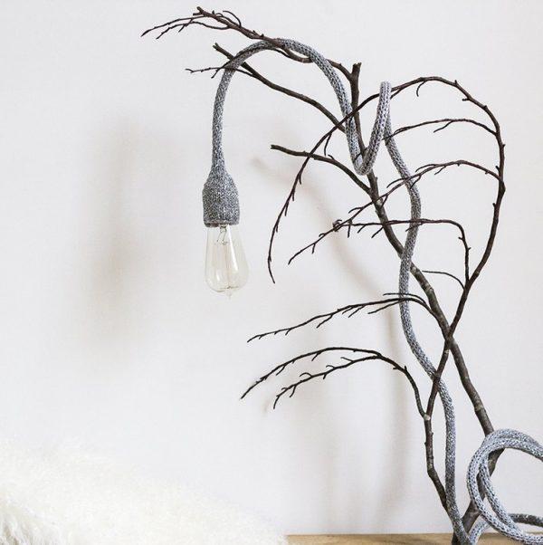 lampe baladeuse gris argenté disposée sur une branche d'arbre