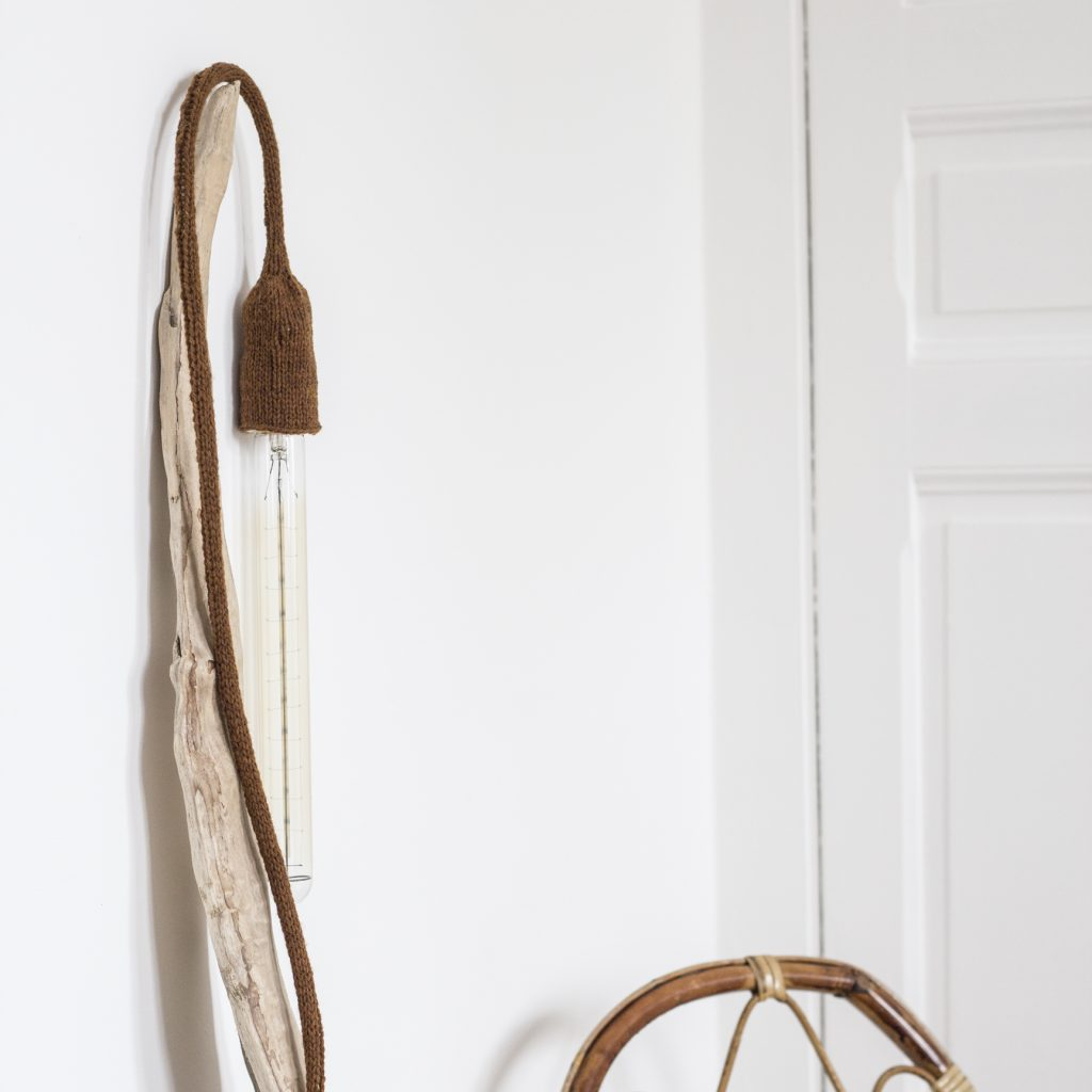 lampe baladeuse coloris terre d'ombre, disposée sur un bois flotté