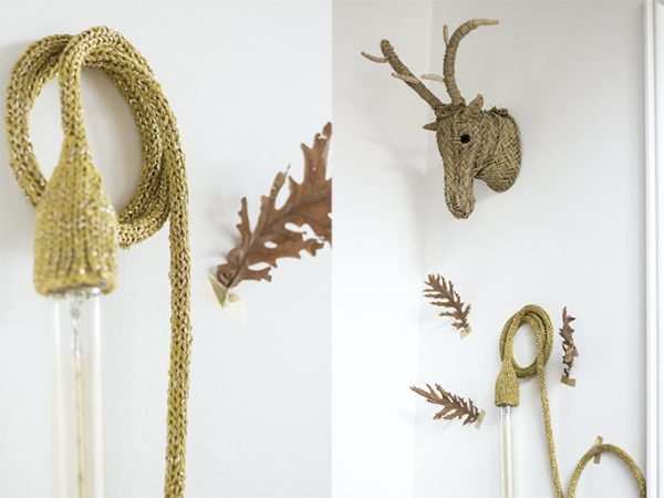 lampe baladeuse tricotée main en coloris moutarde, suspendue au mur par une vis avec trophée tête de cerf en esparto