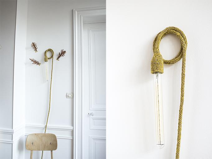 lampe baladeuse tricotée main en coloris moutarde, suspendue au mur par une vis