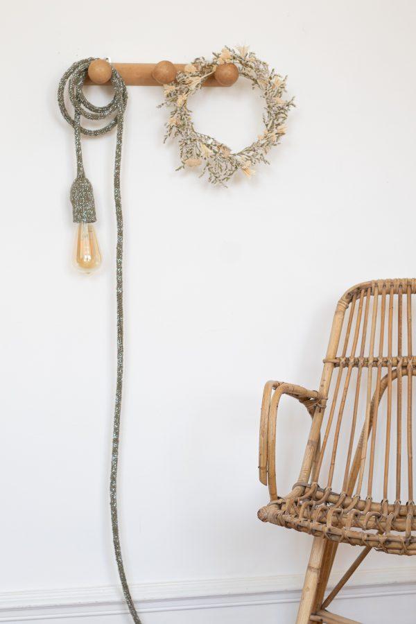 Lampe baladeuse Trendy Little vert argenté présentée sur une patère en bois vintage