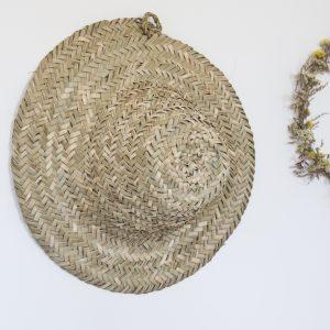 Chapeau de palme tressée à la main, accroché au mur comme décoration.