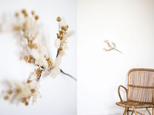 Branche composée de fleurs séchées, à accrocher au mur. Création Trendy Little.