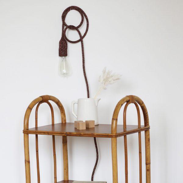 Lampe baladeuse tricotée avec un fil lurex cuivre, accrochée au mur à l'aide d'un petit clou. Création Trendy Little