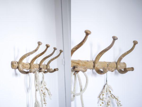 Porte-manteaux en bois patiné avec 4 crochets arrondis.