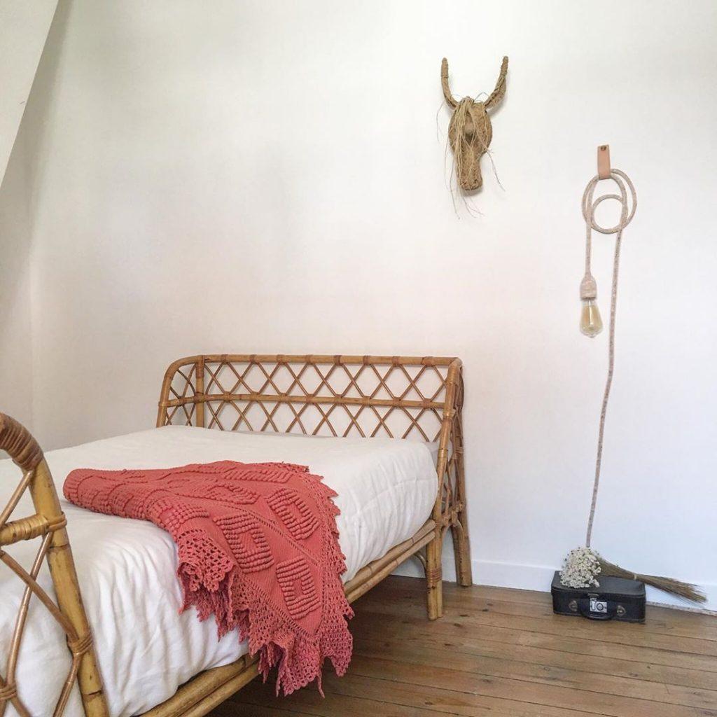 Chambre enfant avec lit en rotin vintage, lampe baladeuse, trophée mural de licorne et plaid en crochet terracotta, par Trendy Little