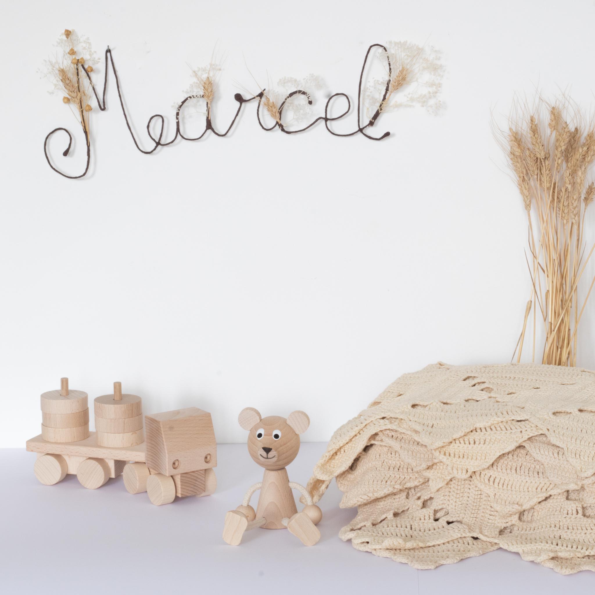 Prénom Marcel en fleurs séchées pour cadeau de naissance original, accroché au mur à l'aide d'un petit clou. Création Trendy Little